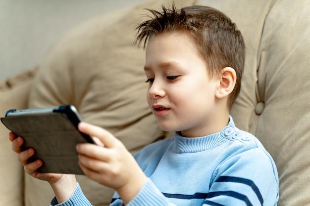 Gelukkige jongen van schoolleeftijd in blauwe sweaterzitting op bank met draadloze tablet.