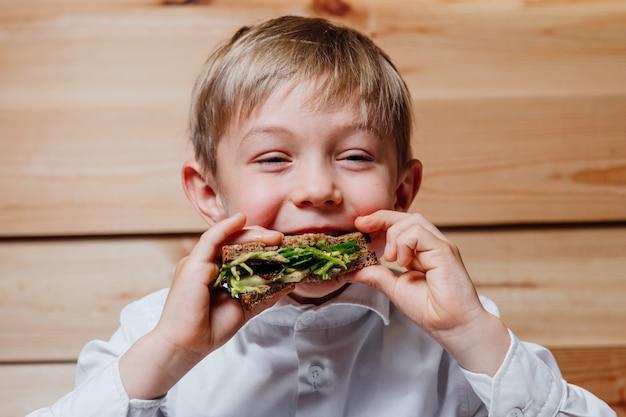 Gelukkige jongen veganistisch broodje eten
