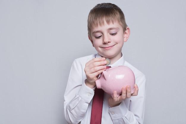 Gelukkige jongen zet een munt in een roze spaarvarken. bedrijfsconcept.