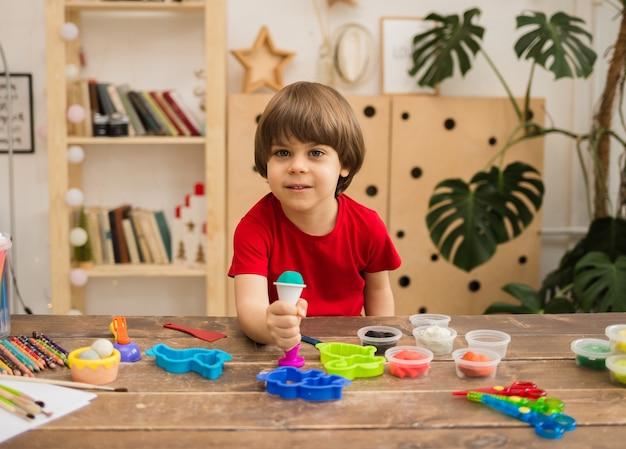 Gelukkige jongen zit aan een tafel met plasticine in de kamer en kijkt naar de voorkant