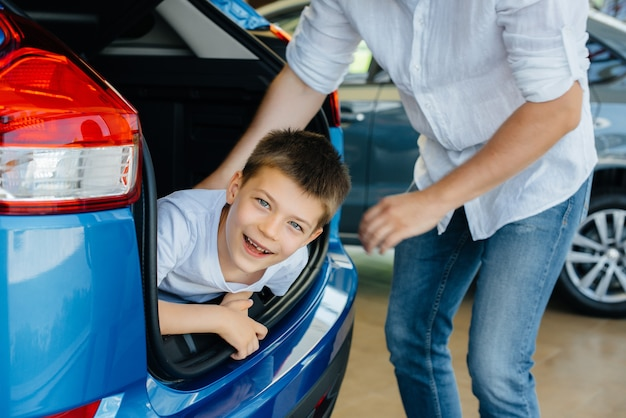 Gelukkige jongen zit in de kofferbak van een nieuwe auto bij een dealer