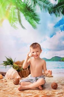 Gelukkige jongen zit te zonnebaden op een zandstrand met palmbomen aan zee