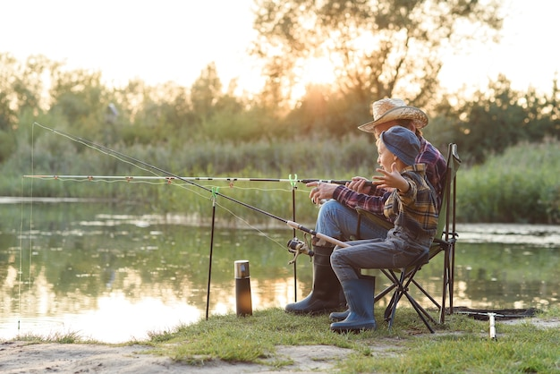Gelukkige jongen zittend op stoelen samen met zijn ervaren oude grijsbaard opa en vissen met hengels op het meer.