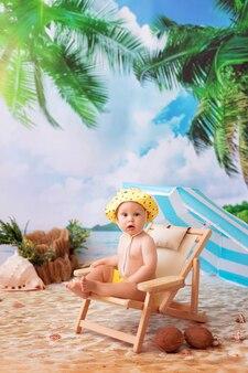 Gelukkige jongen zonnebaden op een houten ligstoel op een zandstrand aan zee onder een parasol