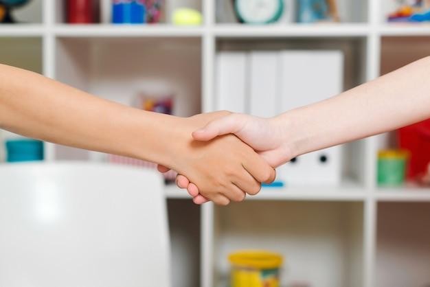 Gelukkige jongens die elkaars hand schudden en elkaars hand vangen.