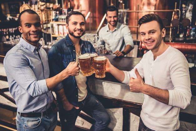 Gelukkige jongens drinken bier en kijken naar de camera.