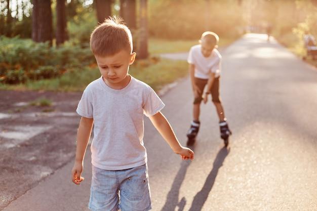 Gelukkige jongens met rolschaatsen rijden op de weg in het park, zomer, kleine jongen met geconcentreerde expressie die rolschaatsen leert met broer, kinderen die casual kleding dragen.