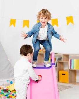 Gelukkige jongens spelen met speelgoed naast glijbaan