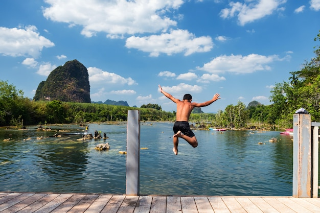 Gelukkige jongenssprong naar rivier in klong rood, krabi