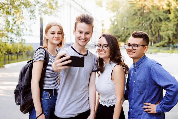 Gelukkige jongerenstudenten die selfies in het park nemen na lezingen