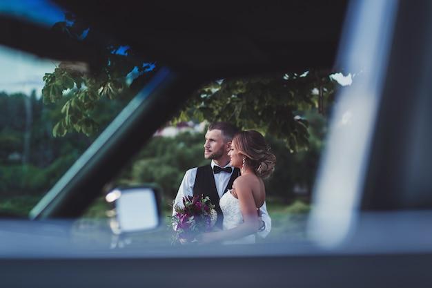Gelukkige jonggehuwden dichtbij huwelijksauto in openlucht