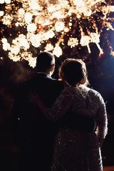 Gelukkige jonggehuwden die het vuurwerk bekijken