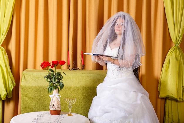 Gelukkige joodse bruid in een weelderige witte jurk, gesluierd gezicht biddend voor geluk in het huwelijk vóór de hupa-ceremonie. horizontale foto