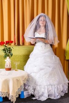 Gelukkige joodse bruid in een weelderige witte jurk, gesluierd gezicht biddend voor geluk in het huwelijk vóór de hupa-ceremonie. verticale foto