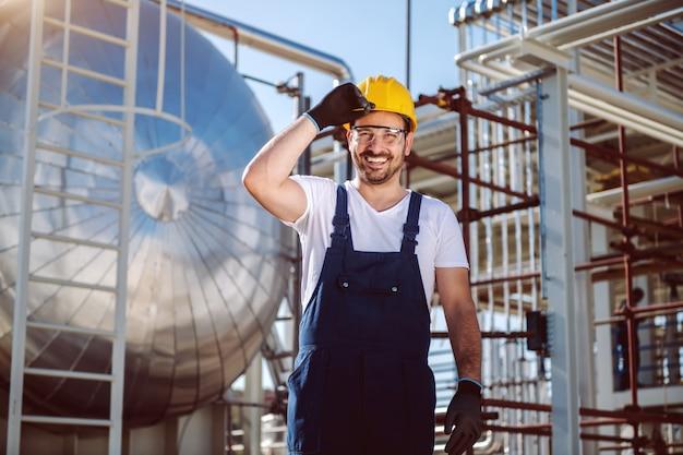Gelukkige kaukasische arbeider in het algemeen en met helm bij het hoofd stellen voor olieopslagtank.