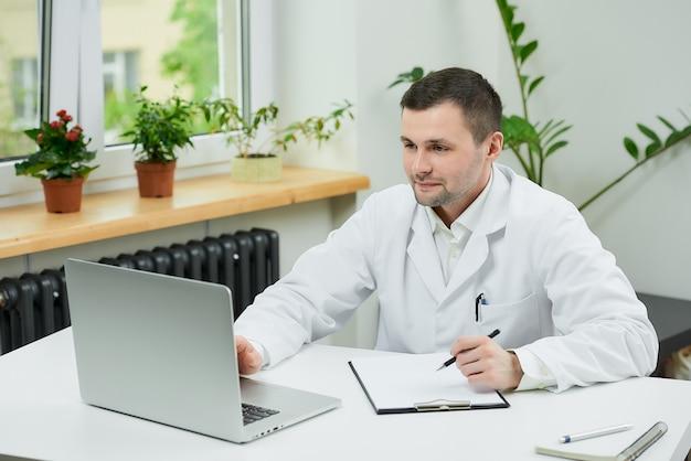 Gelukkige kaukasische arts die in witte laboratoriumlaag aan een patiënt op een online vergadering luistert