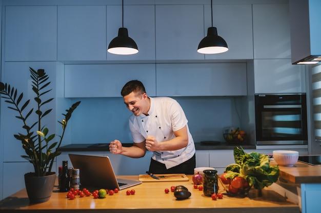 Gelukkige kaukasische chef-kok in witte eenvormige status in keuken en laptop bekijken.
