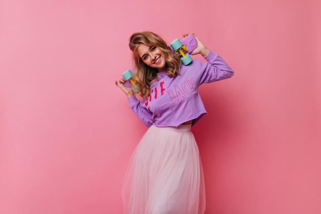 Gelukkige kaukasische dame die pret heeft. enthousiast blond meisje met skateboard staande op roze.