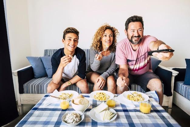 Gelukkige kaukasische familie lunchen samen thuis, tv kijken
