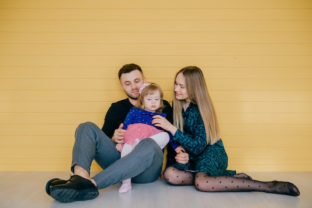 Gelukkige kaukasische familie met één kind dat en pret samen over gele houten muur speelt heeft