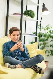 Gelukkige kaukasische jongen die vrijetijdskleding draagt die comfortabel op de gele bank met een smartphone in zijn handen zit en glimlacht