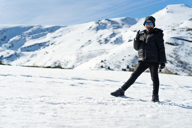 Gelukkige kaukasische jongen die warme kleren draagt op de besneeuwde berg in de winter