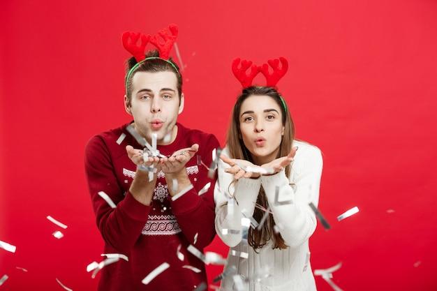 Gelukkige kaukasische man en vrouw in rendierhoeden die kerstmis het roosteren met champagnefluiten vieren, die op kerstmis gelukwensen.