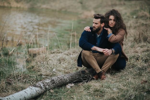 Gelukkige kaukasische minnaars zitten aan de oever van het meer. een bebaarde man en een gekrulde vrouw verliefd. valentijnsdag.