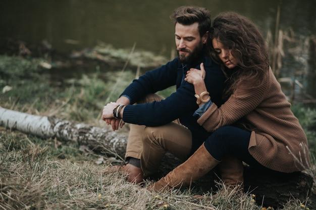 Gelukkige kaukasische minnaars zitten aan de oever van het meer. jong koppel is knuffelen op herfstdag buitenshuis. een bebaarde man en een gekrulde vrouw verliefd. concept van liefde en familie.