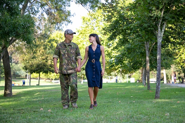 Gelukkige kaukasische paar hand in hand en samen wandelen op gazon in park. man met militair uniform, kijkend naar zijn mooie vrouw en lachend. familiereünie, weekend en thuiskomst concept