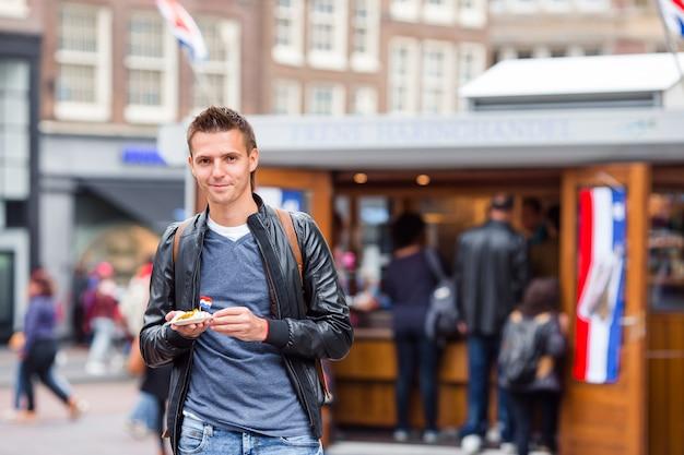 Gelukkige kaukasische toerist met verse haringen met ui en netherlandvlag in amsterdam.