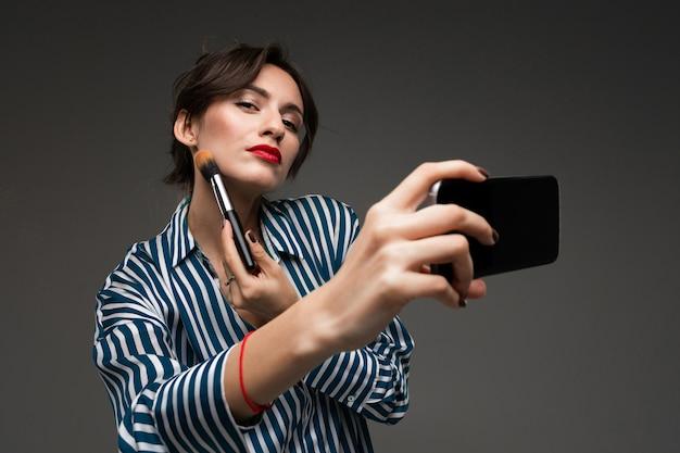 Gelukkige kaukasische vrouw die make-up met borstels doet en een selfie op grijze muur neemt
