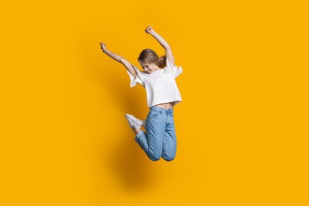 Gelukkige kaukasische vrouw die op een gele gesturing geluk van de studiomuur springt
