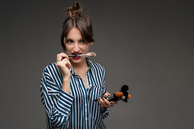 Gelukkige kaukasische vrouw met make-upborstels die op grijze muur wordt geïsoleerd