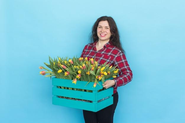 Gelukkige kaukasische vrouwelijke bloemist die en grote doos tulpen op blauw lacht houdt