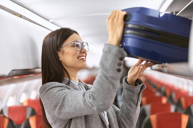 Gelukkige kaukasische vrouwelijke passagier met bagage in vliegtuigsalon