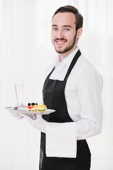Gelukkige kelner die met dienblad camera bekijken