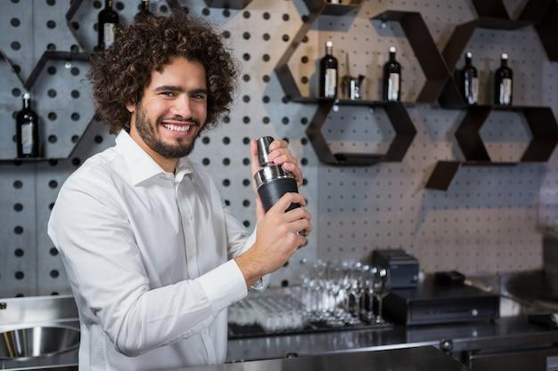 Gelukkige kelner het schudden drank in cocktailshaker in een bar