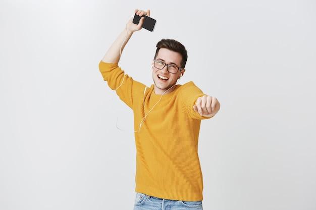 Gelukkige kerel dansen op muziek in oortelefoons, springen en houden van mobiele telefoon
