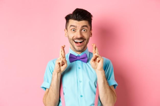 Gelukkige kerel die een wens doet, vingers gekruist voor geluk en glimlachend in de camera, wachtend op goed nieuws, staande over roze.