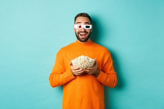 Gelukkige kerel die films in 3d bril bekijkt, popcorn eet en camera bekijkt, die zich over lichtblauwe achtergrond bevindt. kopieer ruimte
