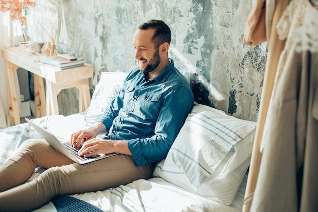 Gelukkige kerel die op het toetsenbord van de laptop typt en glimlacht terwijl hij thuis blijft tijdens pandemische quarantaine