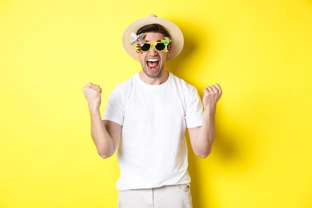 Gelukkige kerel die op vakantie gaat, wint of viert, zomerhoed en zonnebril draagt. toeristische zoekt opgewonden, staande tegen gele achtergrond.