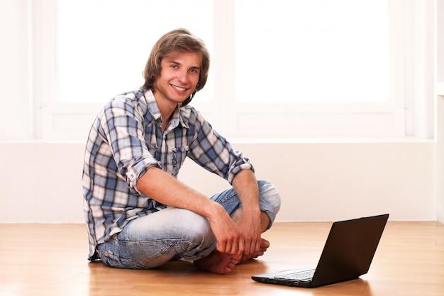Gelukkige kerel die thuis met laptop ontspant