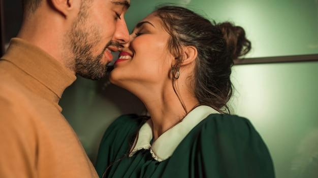 Gelukkige kerel die vrolijke dame kussen dichtbij muur