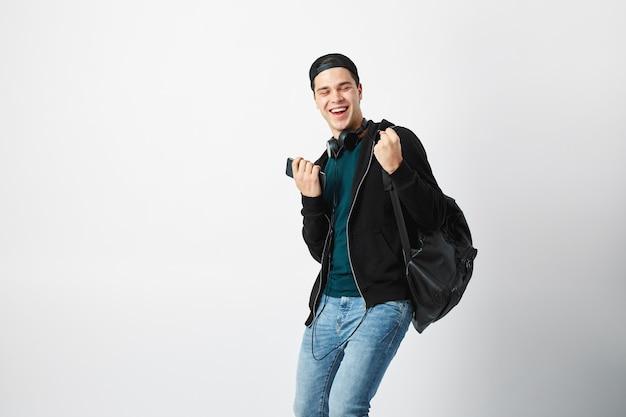 Gelukkige kerel gekleed in een donkere t-shirt jeans sweatshirt en een pet a