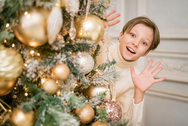 Gelukkige kerel in trui bij kerstboom versiert en kijkt van achteren hebben een gelukkige tijd op c...