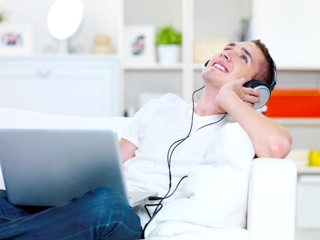 Gelukkige kerel luisteren muziek in hoofdtelefoon van laptop en liggend op de bank
