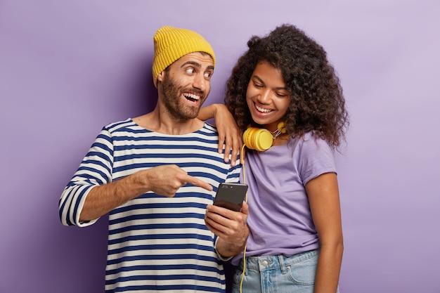 Gelukkige kerel met gele hoed en gestreepte trui, legt aan afro-meisje uit hoe ze een nieuwe applicatie op de smartphone moet gebruiken, wijst op het display, staat dicht, kan zich geen leven voorstellen zonder moderne technologieën.
