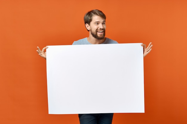 Gelukkige kerel met mockup in hand poster oranje achtergrond